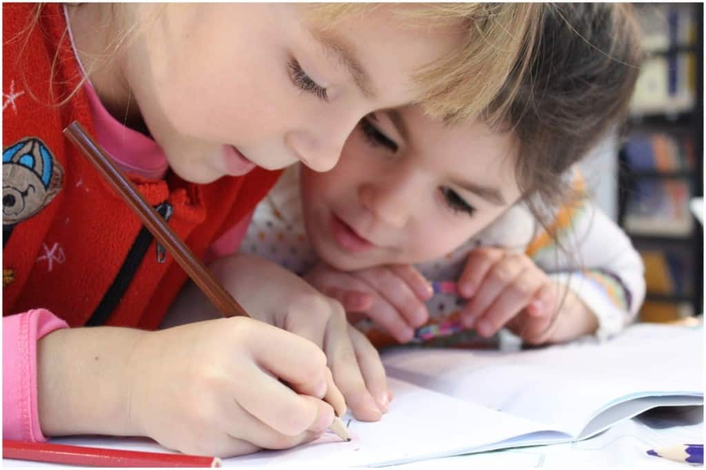 two children doing writing during homeschool