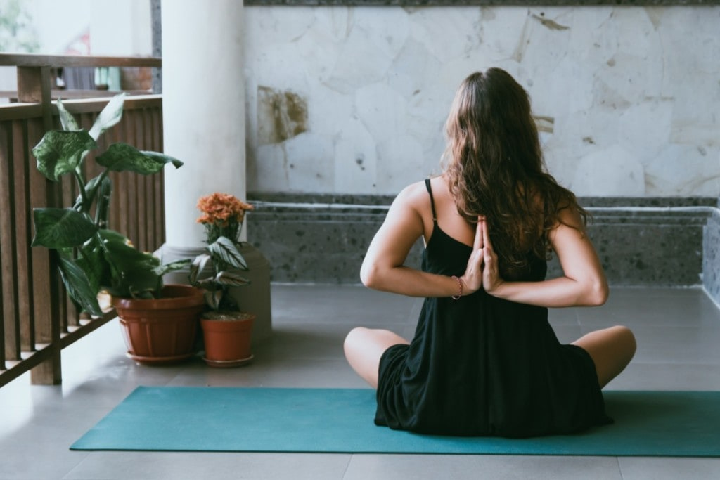 A lady practicing yoga in her space she created as part of her backyard oasis