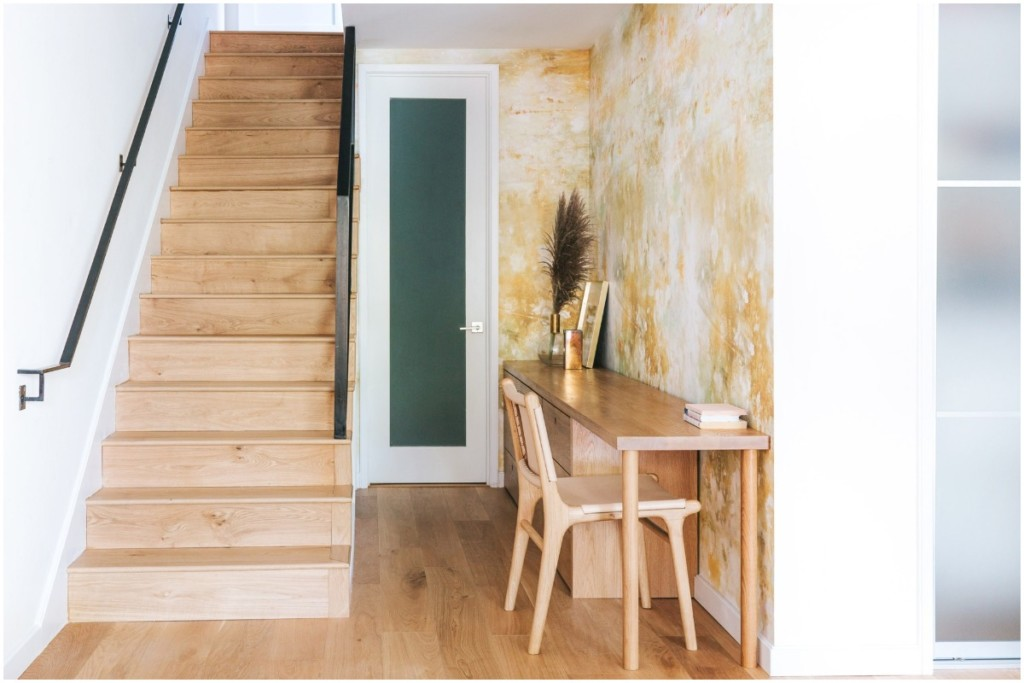 wood stair case hallway with wood desk and chair