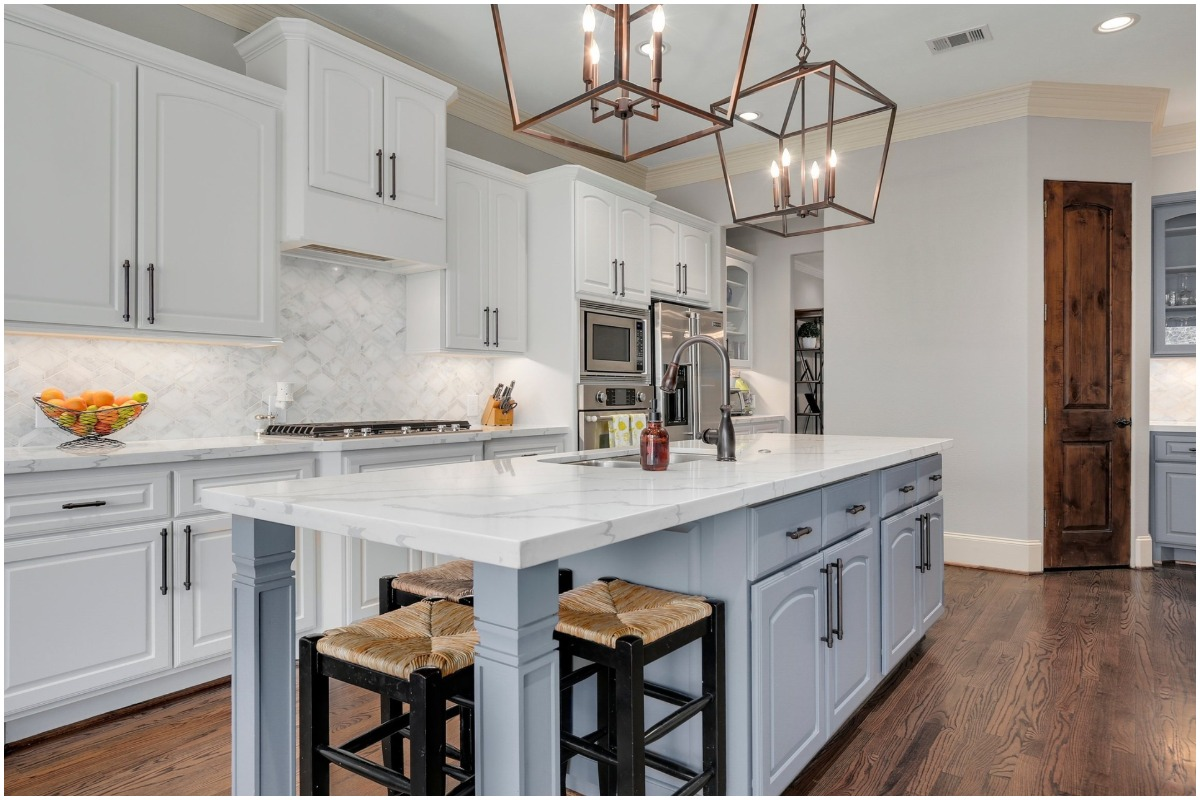white kitchen marble countertops light blue cabinetry woven stools
