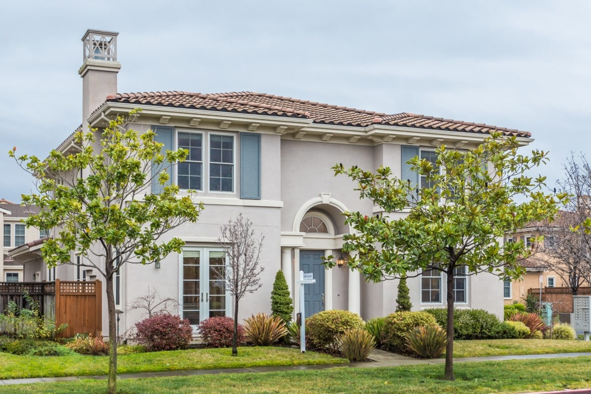 Two story home with blue shutters and front door