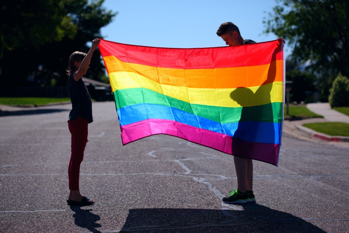 Two people holding up a Pride flag to show their support